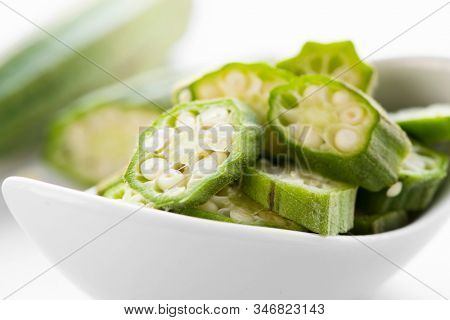 closeup of some chopped raw okra pods in a white ceramic bowl on a white stone surface
