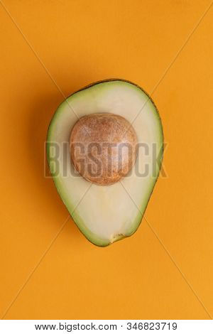 Half Of Avocado On Orange Background. Wholesome Tropic Fruit