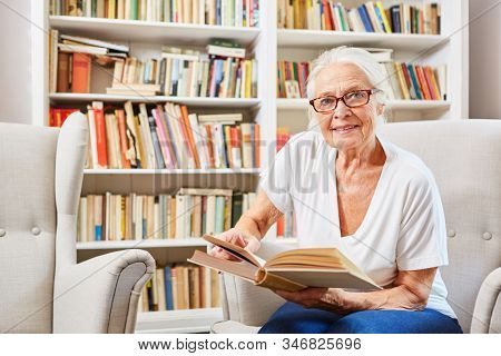 Curious senior citizen in the library reads a book for knowledge and training