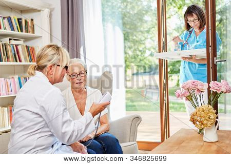 Female doctor checks the blood pressure of a senior citizen in her senior citizen apartment