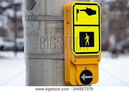 A Modern Yellow Pedestrian Call Button Is Mounted On A Metal Traffic Signal Pole And Seen In Winter.