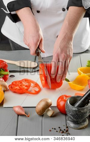 Chef Cook Slicing A Red Bell Pepper On A White Board