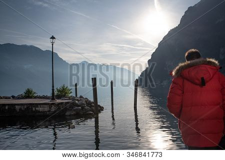 Man Dressed In Red Admires The View Of Lake Garda.