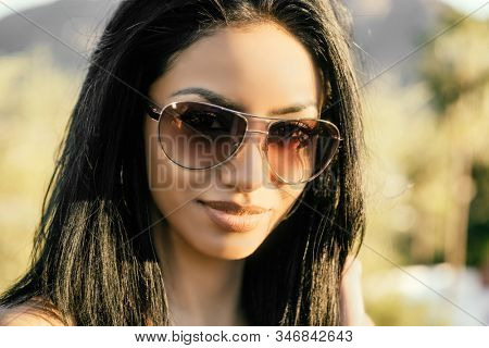 Portrait of attractive woman wearing sunglasses outside,
