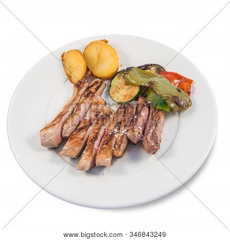 A Dish Of Iberico Pork Secreto With Baked Potatoes And Some Vegetables On A White Background
