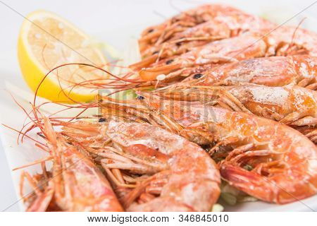 A Grilled Jumbo Shrimp Dish With Lemon And Lettuce