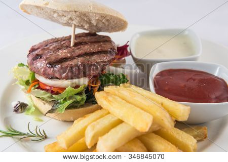 The Detail Of A Hamburger With Vegetables And Fries On A Plate