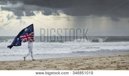 Australian Flag Blowing In The Wind Held By A Female Jogging On A Aussie Beach,