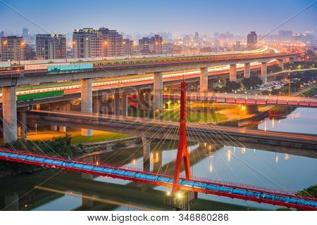 Taipei, Taiwan bridges and roads over the Keelung River at dusk.