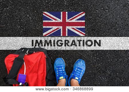 Man In Shoes With Bag Standing Next To Line With Word Immigration And Flag Of United Kingdom On Asph