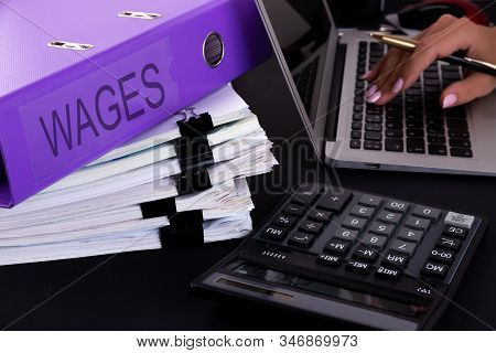 A Business Woman Is Surrounded By Large Bundles Of Documents. Above Is A Purple Folder With The Word