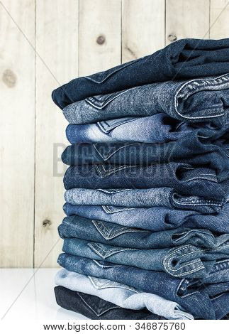 Jeans Stacked On A Wooden Background For Design