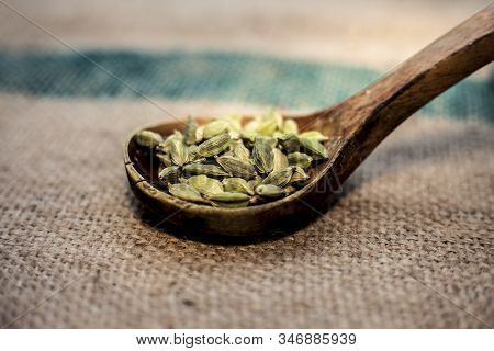 Close Up Of Raw Green Colored Fresh Cardamom, Cardamon, Cardamum Or Ealichi In A Wooden Scoop On A B
