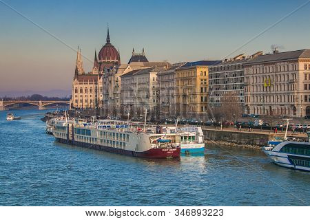 Budapest, Hungary - January 1, 2020: View Of Ferry In The Danube River And The Parliament Building I