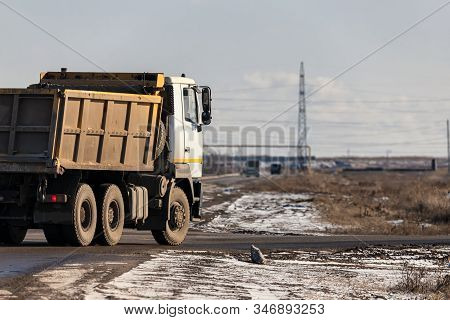 An Old, Dirty Dump Truck Turns Off The Main Road