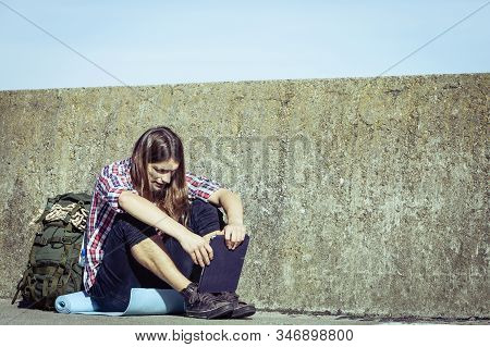Man Tourist Backpacker Relaxing Outdoor Sitting By Grunge Wall Using Tablet. Internet, Tourism Activ