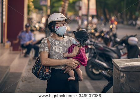 Hue, Vietnam - 2019-06-26: On The City Street, A Young Mother With A Baby In Her Arms Masked On Her