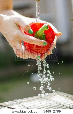 Close-up Image Of Woman Washing Red Bell Paprica On Sink
