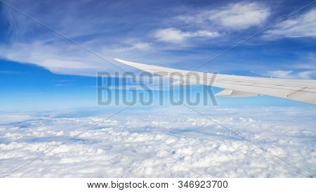 Window View Of Airplane Wing Fly Over  The Blue Sky And White Cloud