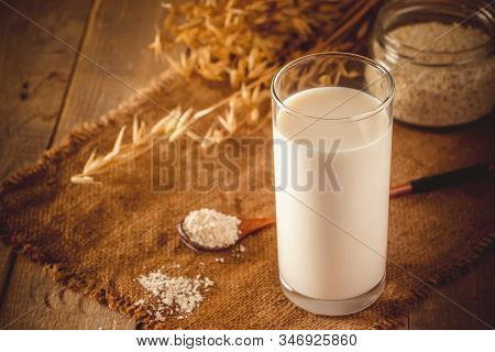 Glass Of Oat Milk On A Wooden Background. Lactose-free Vegetable Diet Milk. Gluten Free Oat Drink On