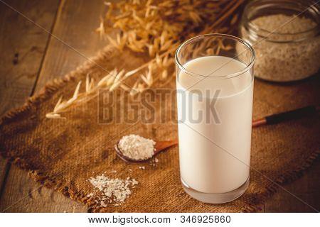 Glass Of Oat Milk On A Wooden Background. Lactose-free Vegetable Diet Milk. Gluten Free Oat Drink On
