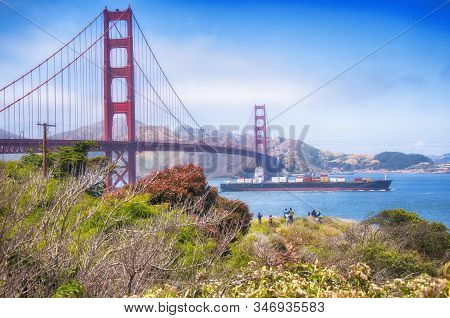 A Cargo Ship Traveling Underneath The Iconic Golden Gate Bridge With The Marin Hills In The Backgrou