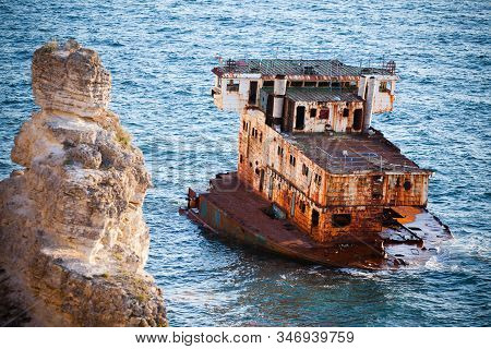 Sunken Rusty Cargo Ship In Still Blue Sea Waters With Rocks Around On Summer Clear Day. Still Landsc
