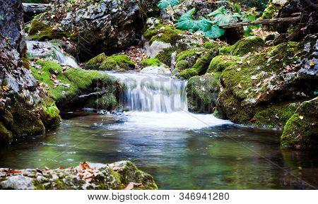 Small Waterfall And Green Clear Still Water Lagoon Surrounded By Green Grass Hills On Summer Day. Tr