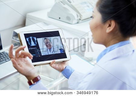 Unrecognizable Female Doctor Taking Part In Online Conference With Her Colleagues Using Her Pad