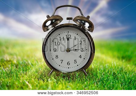 Daylight Saving Time Concept. Alarm Clock In Green Grass With Blue Sky And Sunbeams In Background.