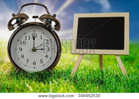 Old Vintage Alarm Clock With Chalk Board. Turn Time Forward For Sommer Time. Daylight Saving Concept