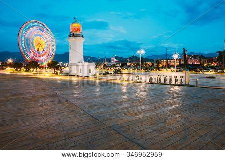 Batumi, Adjara, Georgia - May 26, 2016: Ferris Wheel In Motion And Pitsunda Lighthouse At Promenade
