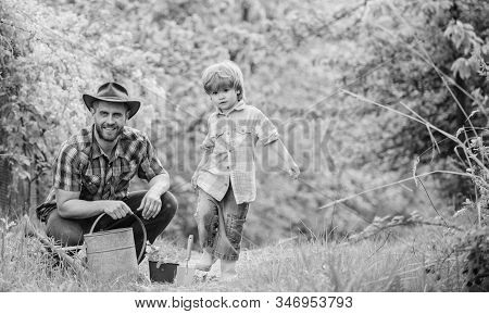 happy earth day. Family tree nursering. Eco farm. small boy child help father in farming. watering can, pot and hoe. Garden equipment. father and son in cowboy hat on ranch. Joyful process poster