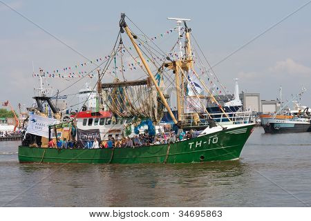A  decorated fishing ship is leaving the harbor during a National fisheries festival