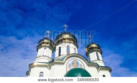 White Orthodox Church Against The Blue Sky.three Domes With Crosses. Golden Domes Of The Church , An