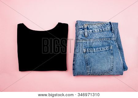 New Black Cotton T-shirt And Blue Jeans Flat Lay On Trendy Pink Background. Minimal Style Clothes. S