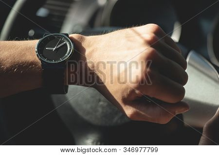 Driver Is Looking On His Wrist Watch Close Up.
