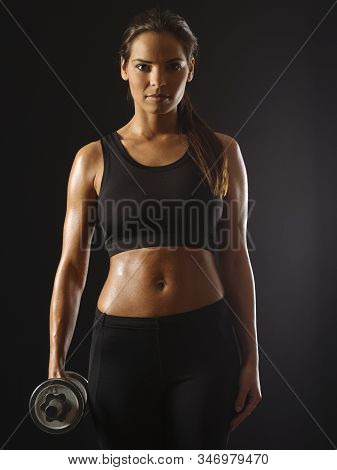 Beautiful Toned Young Woman Exercising With A Dumbbell Over A Dark Background.