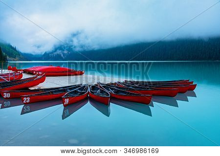 Beautiful Red Canoes Docked At Lake Louise In Foggy Morning, Alberta, Canada