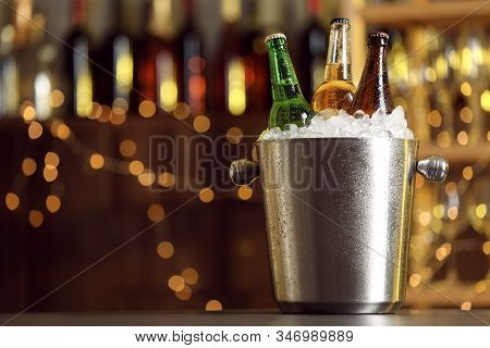 Beer In Metal Bucket With Ice On Table Against Blurred Lights. Space For Text