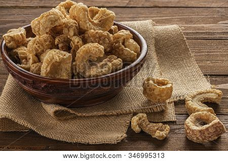 Foreground Of Some Pork Rinds In A Brown Bowl On Burlap Fabric And Wooden Table