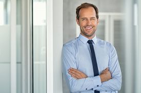 Portrait of a successful leader smiling at modern office with copy space. Happy executive businessman looking at camera at work place. Mature entrepreneur with crossed arms leaning on glass wall.