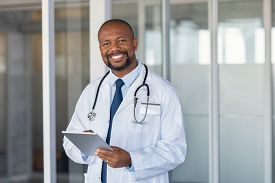 Portrait of confident mature black doctor consulting digital tablet and looking at camera. Smiling african american doctor with stethoscope using tablet at medical clinic. Happy healthcare worker.