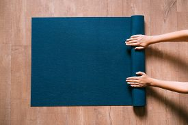 Fit Woman Folding Blue Exercise Mat On Wooden Floor Before Or After Working Out In Yoga Studio Or At