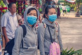 Hue, Vietnam - 2019-06-26: On The City Street, Two Girls In Blindfolds, The Concept Of The Spread Of