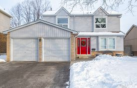 A Winter Scene In Front Of A Suburban Detached House With Grey Siding And Red Door Decorated With A
