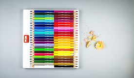 Multicolored Pencils With Sharpener In Box On Gray Background