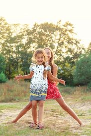 Two Cute Little Girls Embracing And Laughing At The Countryside. Happy Kids Outdoors Concept