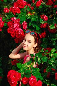 Portrait Of Cute Teenager Girl Smiling At The Roses