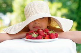 Portrait Of Happy Cute Preteen Girl In Big Hat Is Eating Strawberries At Summer Day
